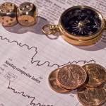 A Stock Market Sheet with Dice, Gold Dollars and a Compass